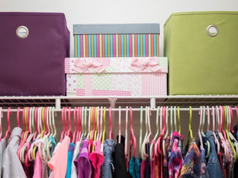 young girl's closet neatly organized with bins and boxes.