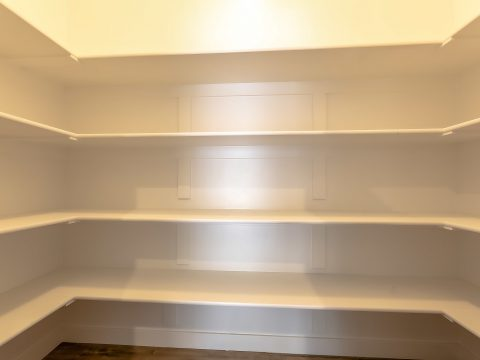 Empty pantry Illuminated small room with empty white painted wooden shelves viewed from an open door