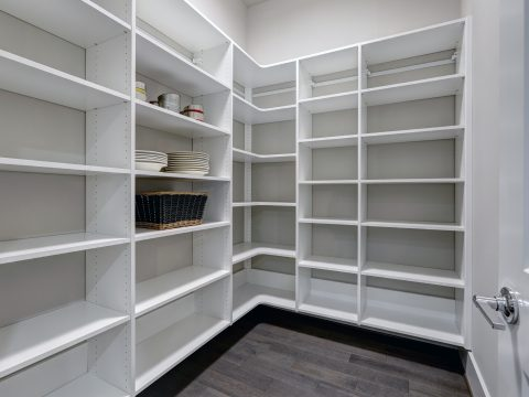 Empty pantry interior with white shelves and dark wood floor. Palm Desert, CA